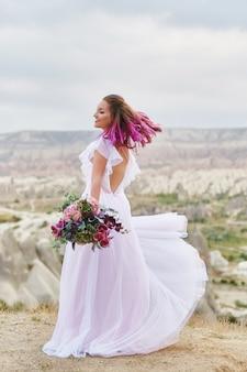 Mulher com um lindo buquê de flores nas mãos dela dança na montanha nos raios do pôr do sol do amanhecer. lindo vestido longo branco no corpo da menina. noiva perfeita com dança de cabelo rosa