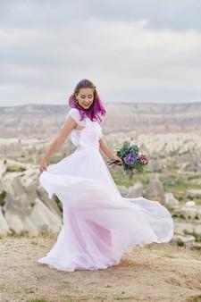 Mulher com um lindo buquê de flores nas mãos dela dança na montanha