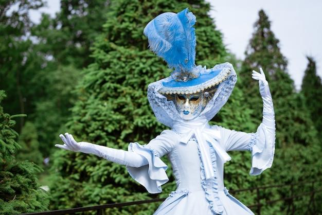Mulher com um lindo vestido azul de carnaval e uma máscara veneziana no parque em um dia ensolarado