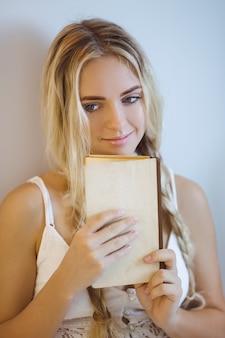 Mulher com um livro descansando em casa
