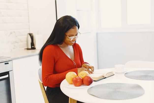 Mulher com um livro e frutas