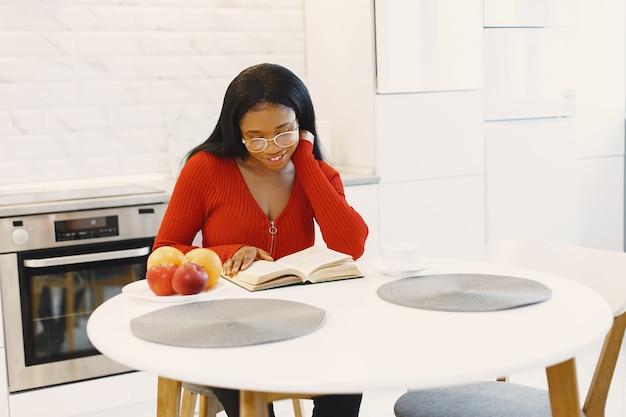 Mulher com um livro na cozinha
