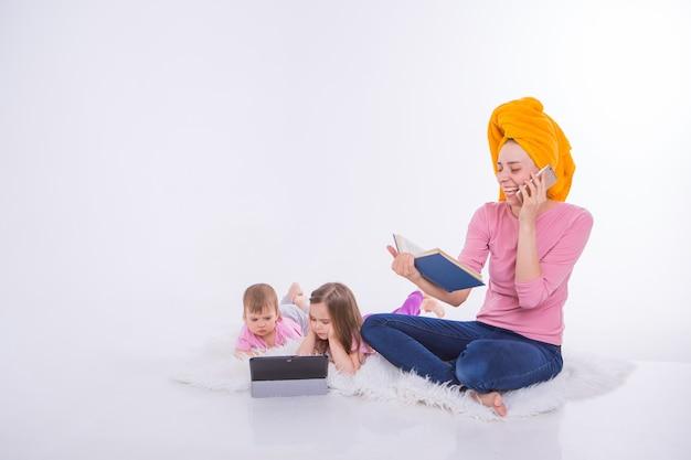 Mulher com um livro nas mãos dela está falando no telefone. crianças assistem desenhos animados em seu tablet. a mãe lavou o cabelo. toalha na cabeça. hobbies e recreação com gadgets.
