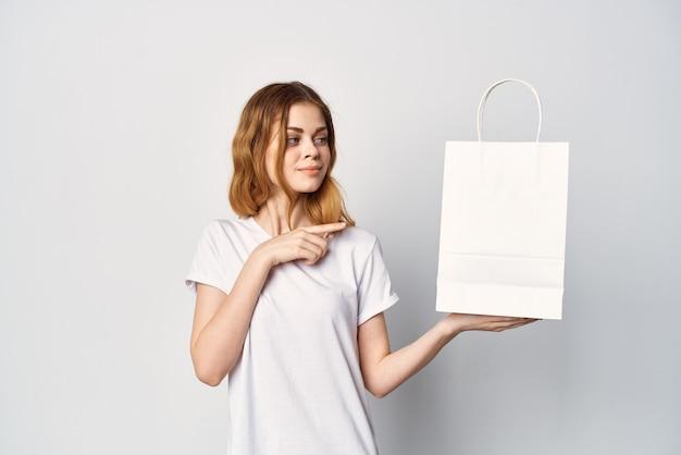 Mulher com um pacote branco nas mãos faz uma compra em uma loja de estilo de vida