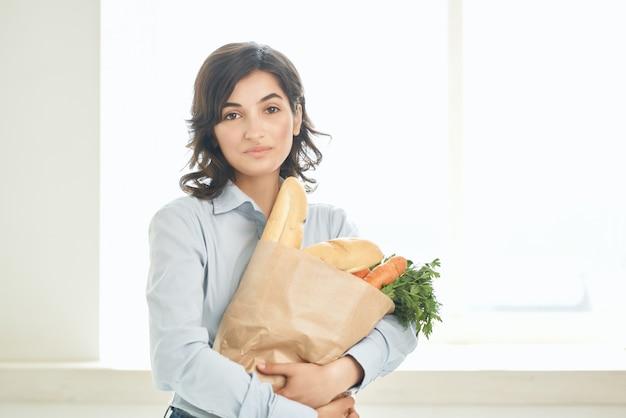 Mulher com um pacote de serviço de entrega de compras de mantimentos