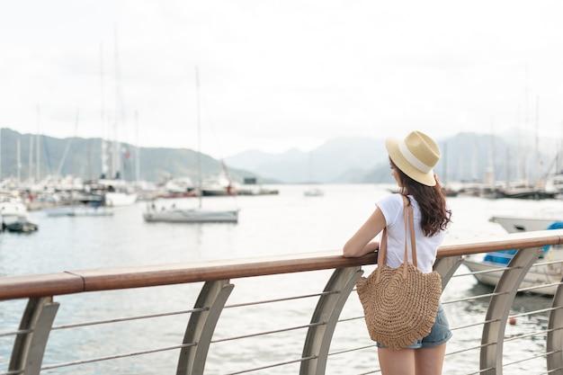 Mulher com um pé de chapéu no porto