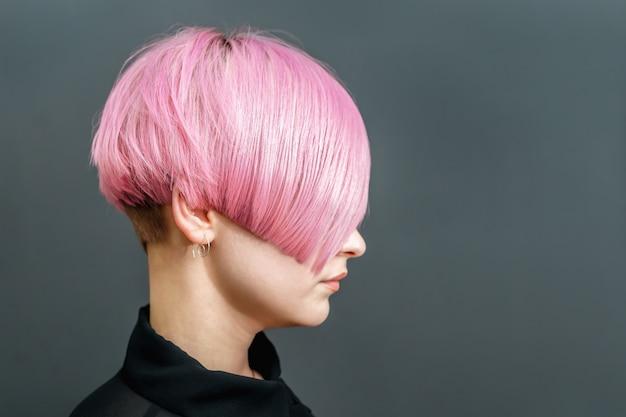 Mulher com um penteado rosa curto.