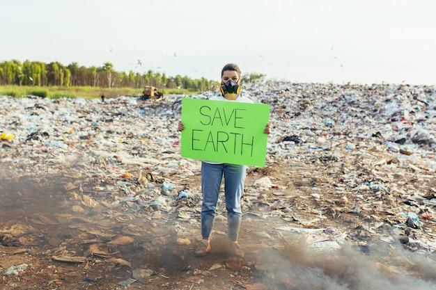 Mulher com um pôster salve o planeta, piquetes de ambiente contaminado com lixo, queimando fogo e fumaça negra