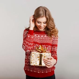 Mulher com um presente no estúdio em um fundo cinza