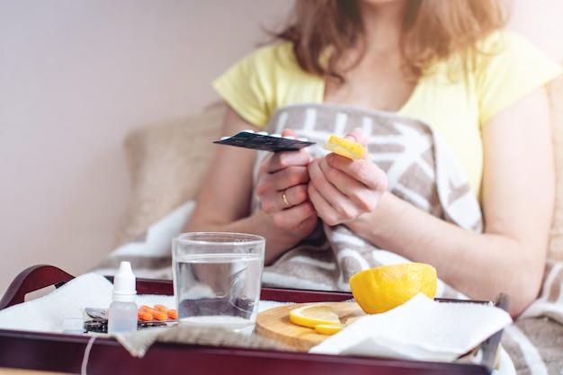 Mulher com um resfriado escolhe entre comprimidos e vitaminas para tratamento
