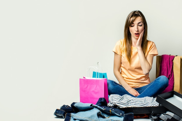 Mulher com um rosto surpreso senta-se no chão, cercado por muitas roupas e sacolas de compras