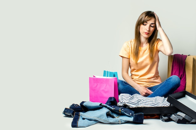 Mulher com um rosto triste senta-se no chão, rodeado por diferentes roupas e sacolas de compras