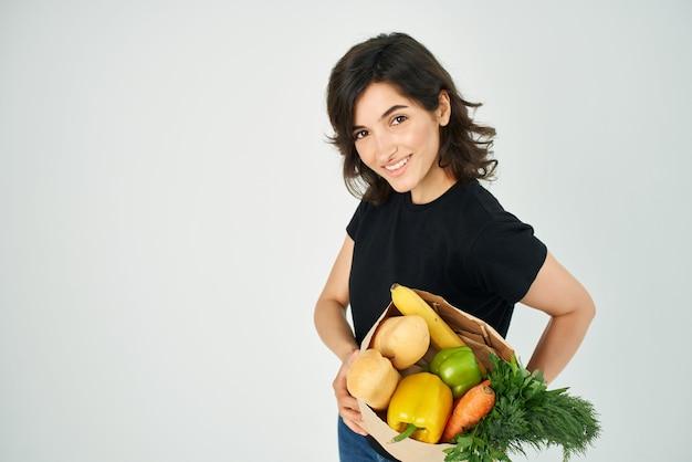 Mulher com um saco de papel com mantimentos nas mãos entregando alimentos saudáveis de vegetais