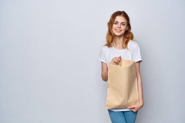 Mulher com um saco de papel nas mãos, comprando moda viciada em compras