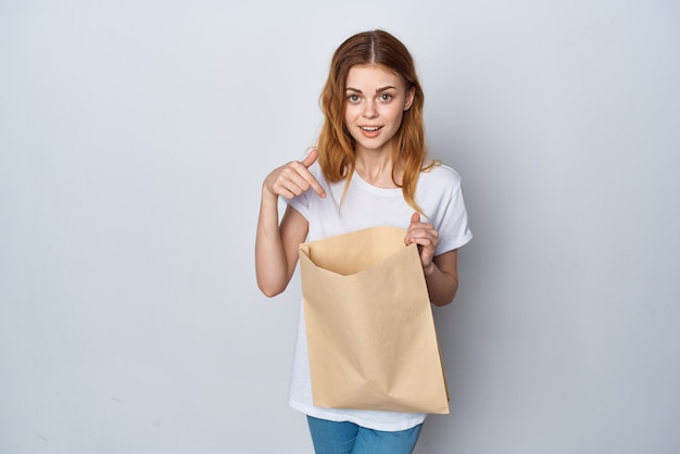 Mulher com um saco de papel nas mãos, comprando um fundo claro divertido