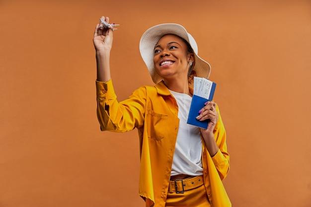 Mulher com um sorriso em um chapéu branco na camisa amarela com um avião de brinquedo com um passaporte com passagens nas mãos. conceito de viagens