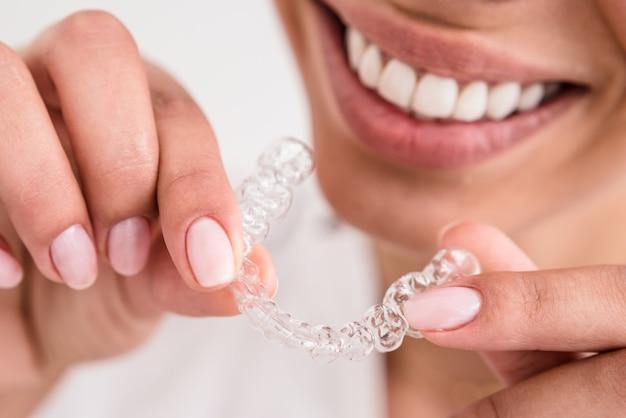Mulher com um sorriso lindo segurando um protetor bucal transparente