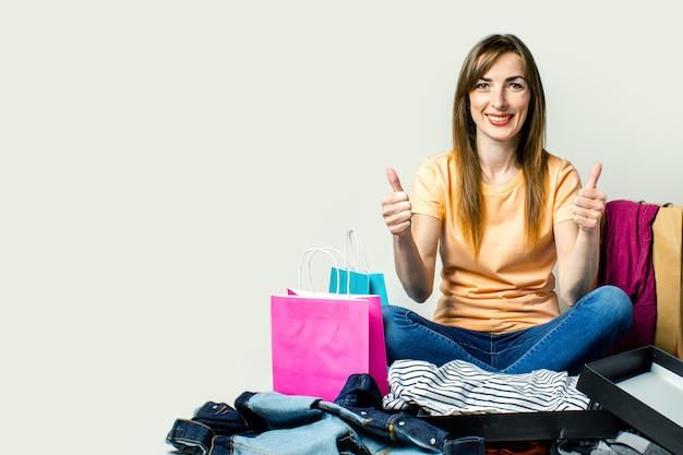 Mulher com um sorriso senta-se no chão, cercado por muitas roupas e sacolas de compras