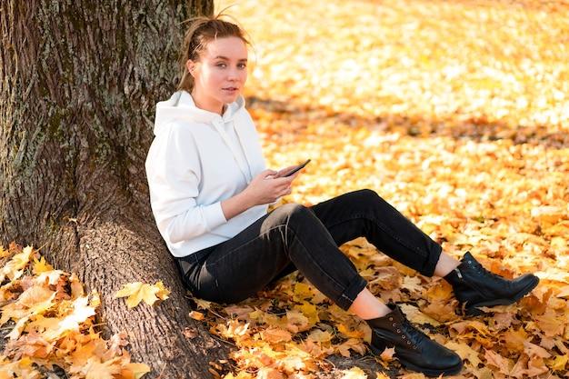 Mulher com um suéter branco com capuz e capuz está sentada no chão do parque e segurando um celular nas mãos. linda garota usa smartphone para comunicação. mulheres enviando mensagens de texto. conceito de comunicação