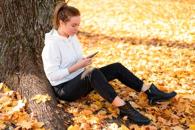 Mulher com um suéter branco com capuz está sentada no chão do parque e segurando um celular nas mãos.