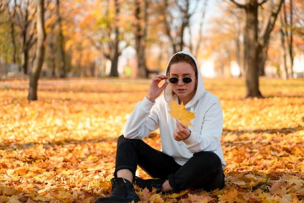 Mulher com um suéter branco com capuz está sentada no chão do parque e segurando uma folha na mão.