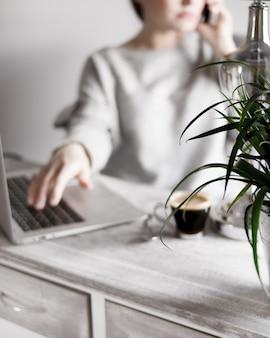 Mulher com um suéter cinza falando ao telefone com a mão em um laptop e café na mesa
