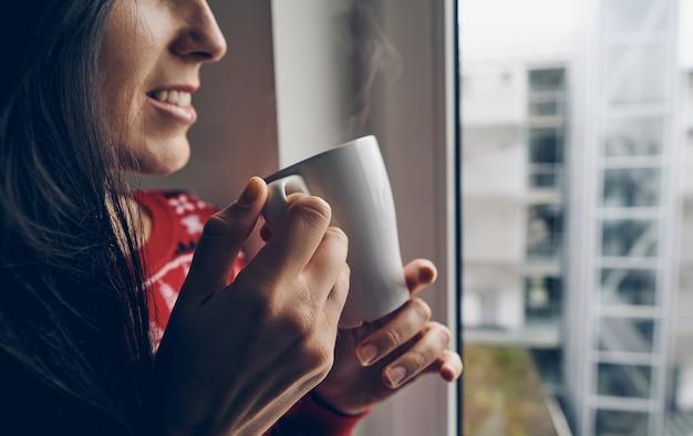 Mulher com um suéter de natal segurando uma caneca perto da janela