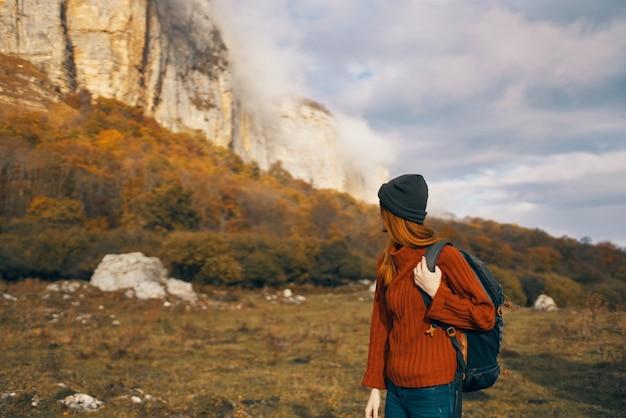 Mulher com um suéter e uma mochila caminhando nas montanhas