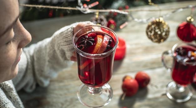 Mulher com um suéter está bebendo vinho quente perfumado com especiarias, decorado com frutas e especiarias e desfrutando de uma noite agradável. conceito de atmosfera festiva acolhedora, clima de ano novo e natal.