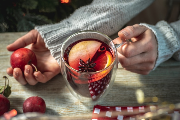 Mulher com um suéter está segurando uma caneca transparente com vinho quente e picante perfumado, decorado com frutas e especiarias. conceito de atmosfera festiva acolhedora, clima de ano novo e natal.