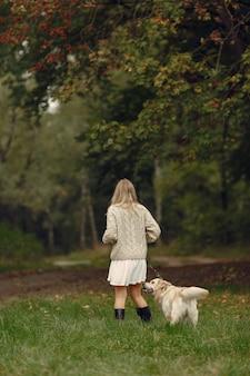 Mulher com um suéter marrom. senhora com um labrador