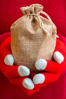 Mulher com um suéter quente e luvas de tricô vermelhas segurando uma sacola de presente de natal
