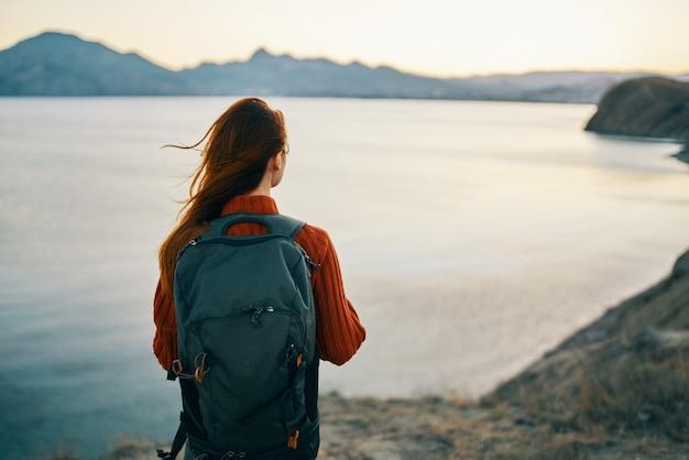 Mulher com um suéter vermelho com uma mochila nas costas nas montanhas na paisagem rochosa da natureza