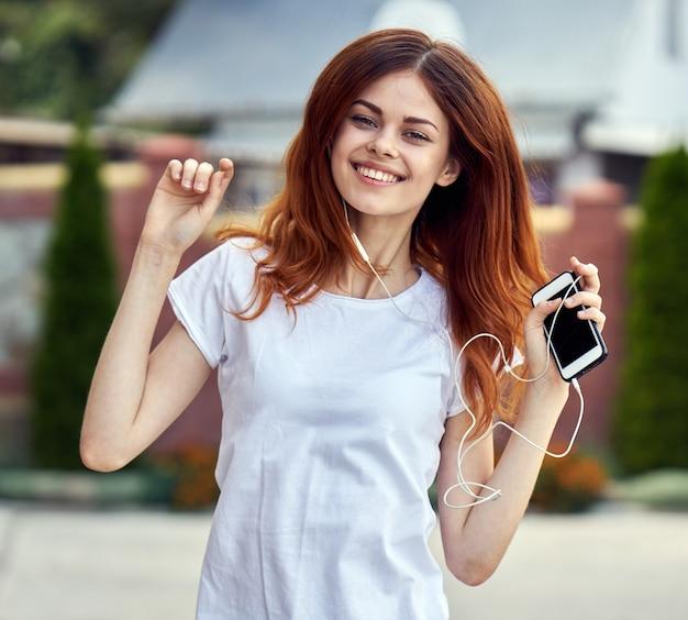 Mulher com um telefone e fones de ouvido