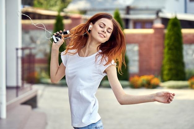 Mulher com um telefone em fones de ouvido é executado