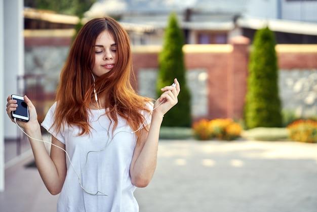 Mulher com um telefone em fones de ouvido no parque