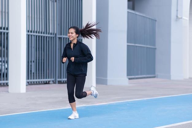Mulher com um terno preto com feliz corrida ou corrida na pista de corrida azul.