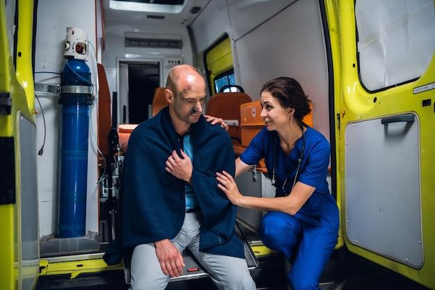 Mulher com um uniforme médico, falando amigavelmente e sorrindo para um homem ferido em um cobertor.