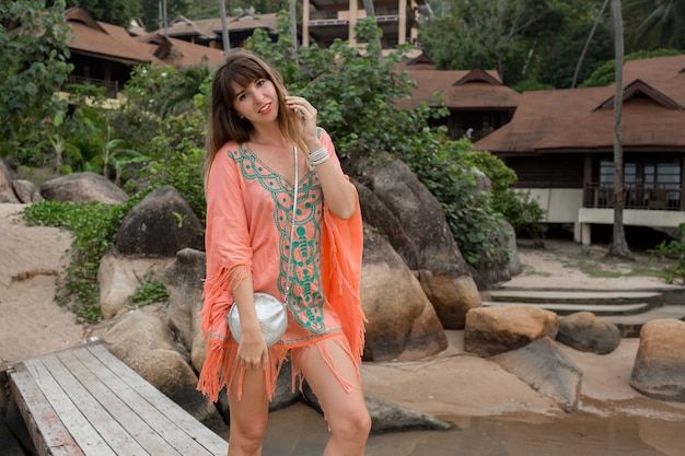 Mulher com um vestido boho, caminhando na praia. pedras e palmeiras no fundo. moda de verão.