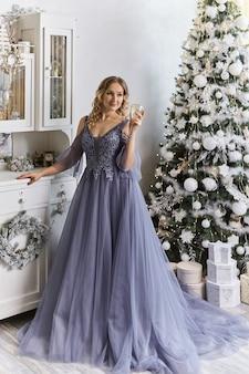 Mulher com um vestido festivo perto da árvore de natal