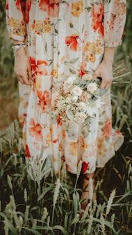 Mulher com um vestido floral segurando um buquê de flores