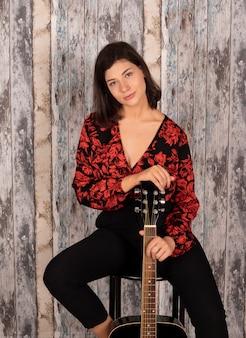 Mulher com um violão sentado em uma cadeira com espaço de madeira