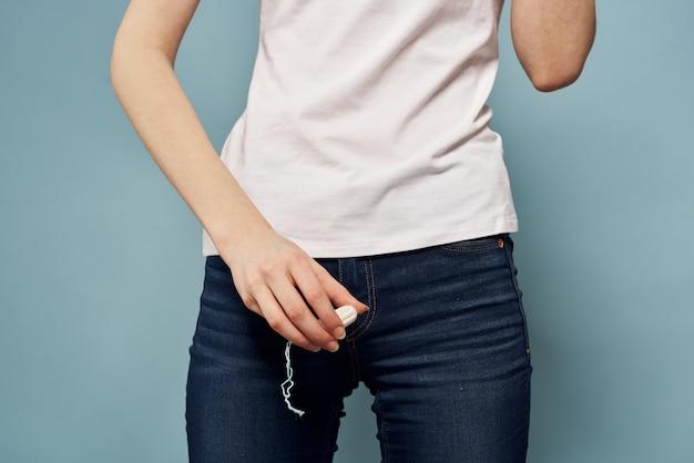 Mulher com uma almofada nas mãos, absorventes e tampões, dias das mulheres