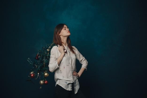 Mulher com uma árvore de natal na mão em uma parede azul e bolas redondas brinquedos od de ano novo.