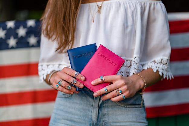 Mulher com uma bandeira americana e passaportes nas mãos dela