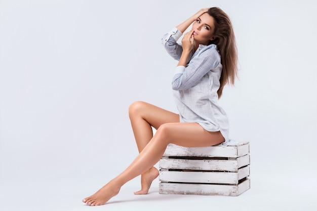 Mulher com uma bela pernas sentado na caixa de madeira