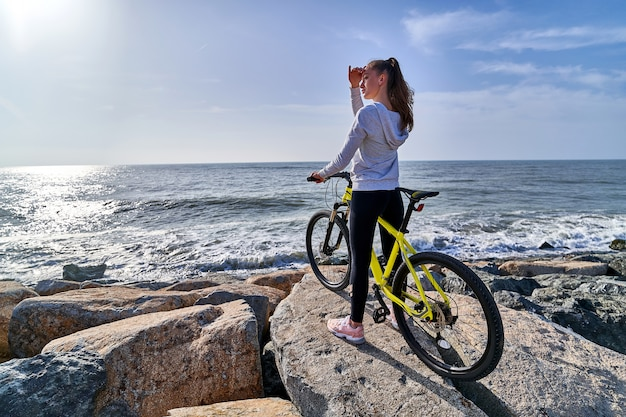 Mulher com uma bicicleta na praia
