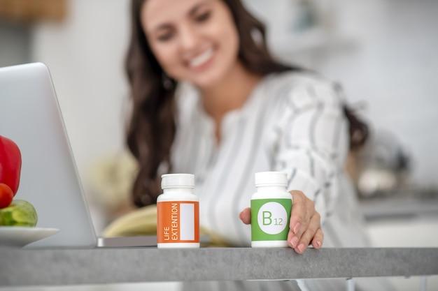 Mulher com uma blusa listrada escolhendo vitaminas