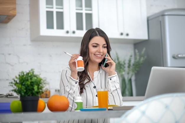 Mulher com uma blusa listrada falando ao telefone