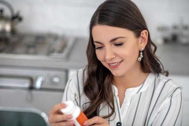 Mulher com uma blusa listrada segurando um frasco de vitaminas nas mãos